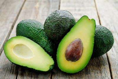 Avocado halbiert und ganz auf Holzuntergrund