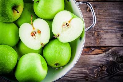 Granny Smith Äpfel in Sieb auf Holzuntergrund
